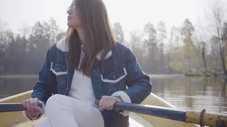independente : Pretty glamour woman in white pants, jeans jacket and sunglasses paddles on the yellow boat on the river, looking around. Girl learning to row. Connection with nature. Active lifestyle Stock Footage