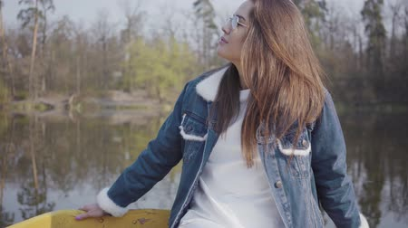 see off : Portrait of young glamour brunette in fashionable glasses and jeans jacket looking in the camera. Beautiful landscape on background Stock Footage