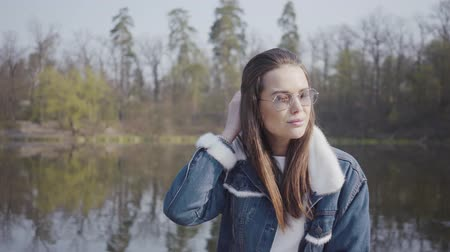 see off : Portrait of pretty young glamour smiling woman in fashionable glasses and jeans jacket looking in the camera. Beautiful landscape on background. Stock Footage