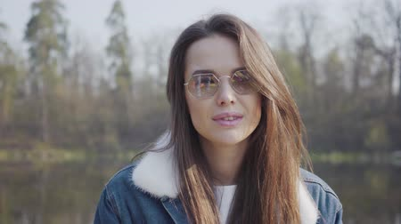 see off : Portrait of pretty young glamour smiling woman in fashionable glasses and jeans jacket looking in the camera. The lady takes off the glasses. Beautiful landscape on background