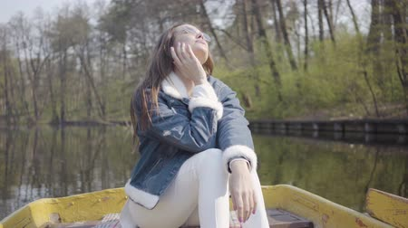 remoção : Pretty glamour woman in white pants and jeans jacket on the boat on the river, enjoying the sun. Beautiful landscape behind. Connection with nature. Active lifestyle. A girl is floating on a boat.