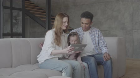 etnia africano : Beautiful young international family at home, african american man, caucasian woman and small girl sitting on the sofa with tablet, looking on the screen. Father hugs mother