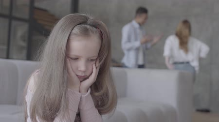 относящийся к разным культурам : Little sad girl sitting on the sofa in the foreground with her head on hands while african ameican father and caucasian mother emotionally talking on the background. Lonely child, family relationship