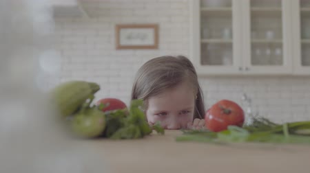 cuketa : Portrait adorable cute little girl looks from the table, hiding looking in the camera. Fresh vegetable zucchini, tomatoes and greens laying on the table. Healthy lifestyle