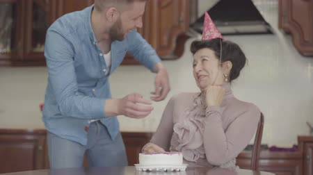 опытный : Mature lady sitting at the table with birthday cap on her head. Adult grandson brings the small cake and puts on the table in front of woman, then hugging the granny, both happy and smiling