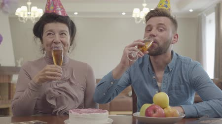 starość : Cute granny and adult grandson clinking the glasses sitting at the table with birthday cap on their heads. Mature woman and younger man drinking juice. Birthday celebration. Family relationship