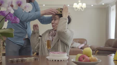 starość : Mature lady sitting at the table in front of small cake and apples on the plate. Adult grandson brings the crown and puts it on the head of woman, then hugging the granny, both happy and smiling