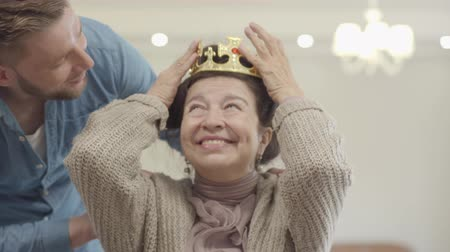 опытный : Portrait of cute pretty mature woman. Adult grandson brings the crown and puts it on the head of granny, Senior lady surprised, she is happy and smiling. Family relationship