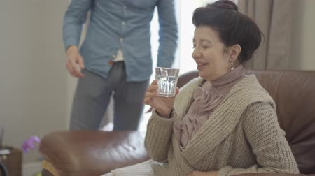 fotel : The mature lady sitting on the leather armchair at home. Adult grandson brings the glass of water and gives it to the woman. The lady saying thank you and smiling. Help, support, love concept