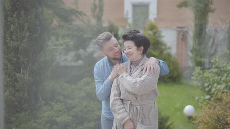 опытный : Portrait happy mature woman standing in the garden in front of the big house, adult grandson hugging her, putting the hand on her shoulder. Tender relationship in family, love, support