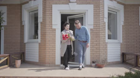 見落とす : Adult grandson and his grandmother holding bouquet of tulips overlook the porch of the big house. The granny telling story to the man, both smiling. Family relationship