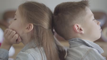 benzer : Close up portrait twin boy and girl sit on the floor of living room back to back angry to each other. Brother and sister relationship. The concept of childrens family love.