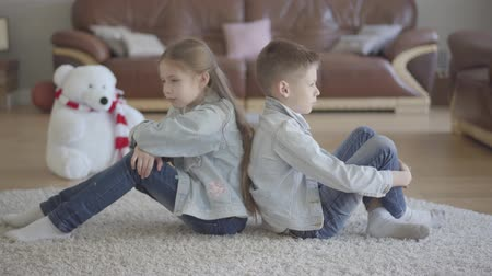 sourozenci : Portrait twin caucasian boy and girl sit on the floor of living room back to back angry to each other. Brother and sister relationship. The concept of childrens family love.