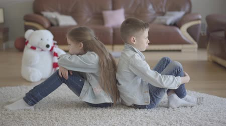 benzer : Twins boy and girl sit on the floor of living room back to back angry to each other. Brother and sister relationship. The concept of childrens family love. Stok Video