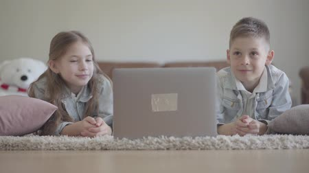 schoolkid : Cute little twins boy and girl lie on the carpet and watching something funny on the computer, laughing and dancing Stock Footage