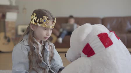 two gender : Cute girl playing with a toy northern bear, dressing him a crown and her twin brother playing laptop on the sofa Stock Footage