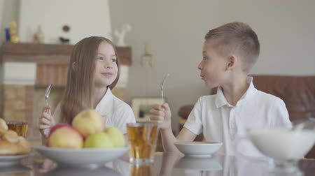 lunchen : Twins brother and sister are sitting at the table in a white shirts before school and knocking with spoons, shouting cheerfully to have food