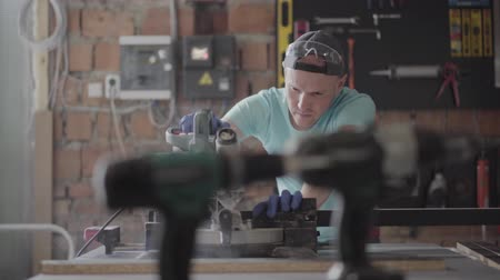 adaptador : The man in protection glasses cutting a wooden board with a small circular saw on the table in the workshop. Furniture factory. Concept of hand manufacturing. Craftman works in a workshop. Stock Footage