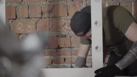 aplikatör : The carpenter in black cap and gloves with tattoos on arms putting glue on the wooden frame for the mirror. The worker using silicone glue gun in furniture manufacturing. Craftman works in a workshop.