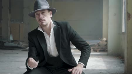 classical suit : Portrait handsome confident man in a hat throws up and catches the coin sitting in an abandoned building. The head of the mafia is waiting in an empty building. Slow motion. Abandoned dilapidated building.