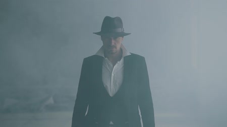 bandido : Portrait brutal gangster in fedora hat and classical suit walk from smoke. Slow motion. Abandoned dilapidated building. Self-confident businessman relaxing