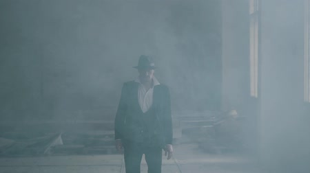 puffing : Portrait confident brutal gangster in fedora hat and classical suit walk from smoke. Slow motion. Abandoned dilapidated building. Self-confident businessman relaxing