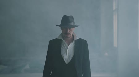 puffing : Portrait confident brutal gangster in fedora hat and classical suit walk from smoke. Slow motion. Abandoned dilapidated building. Self-confident businessman relaxing.