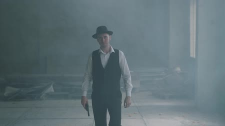 puffing : Handsome confident man in a hat walking to the camera holding a gun in an abandoned building. The head of the mafia is in an empty building. Cool guy, thug, mafia. Slow motion. Stock Footage