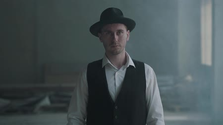 puffing : Portrait handsome confident man in a hat looking to the camera in an abandoned building. Boss of the mafia is in an empty building. Slow motion.