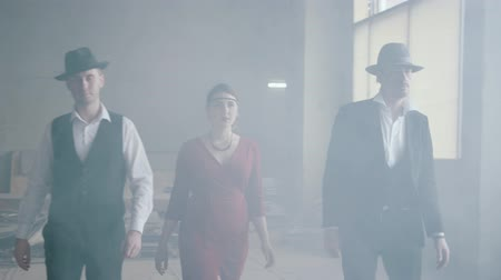 atender : Two confident men in hats and suits and woman in red dress walking forward an abandoned building. The mafia in an empty building. Cool guys, thug, mafia, criminal gang, familia. Slow motion.