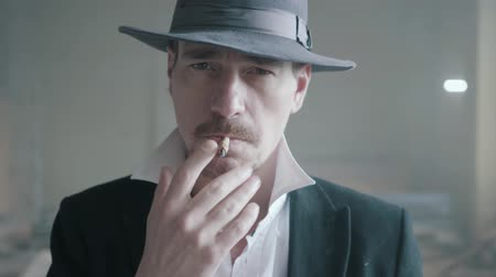 alışkanlık : Handsome confident man in a hat smoking cigar in an abandoned building. The head of the mafia is in an empty building. Criminal authority portrait, close up.