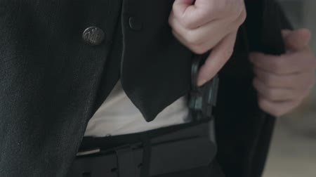 trousers : Man in formal suit and a gun in his belt close up