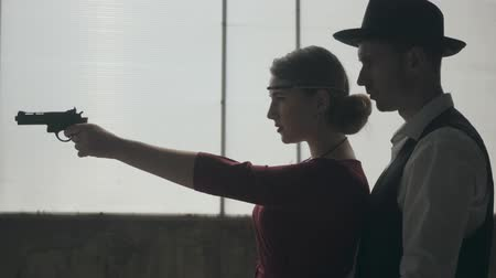 direkt : Elegant young woman in red dress aiming a gun, handsome gallant man stands behind, directing her hand, side view. Happy couple of gangsters. Bonnie and Clyde