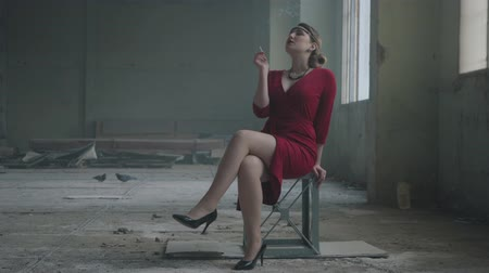 poros : Portrait elegant woman in red elegant dress sitting on the chair in the abandoned building smoking cigarette. Retro, vintage style. Free independent lady. Abandoned dilapidated building. Stock mozgókép