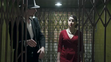 poros : Portrait tall man in the suit and hat opens the door and passes inside the dark room a confident beautiful girl in an elegant red dress. Retro, vintage style. Mafia life