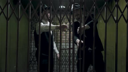 forgery : Two gangsters men in formal suits and fedora hat opening a metal forged gates