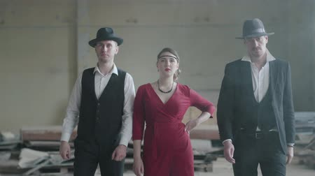 mafia : Two confident men in hats and suits and woman in red dress walking toward the camera in an abandoned building. The mafia in an empty building. Cool guys, thug, mafia, criminal gang Stock Footage