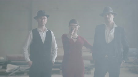 abandonar : Two confident well-dressed men standing in two sides of a woman in red dress, who is aiming a pistol at the camera in an abandoned building. Cool guys, thug, mafia, criminal gang Stock Footage
