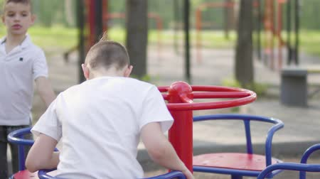 общий : Little boy whirls on a carousel in the park. Boy on the playground riding on the carousel and he is sick or bored. His brother twin running to him