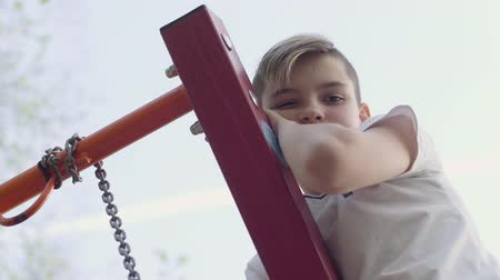 climbed : Blonde boy climbed on a swing and looks into the camera from top to bottom. Active lifestyle, carefree childhood, adorable kid playing outdoors