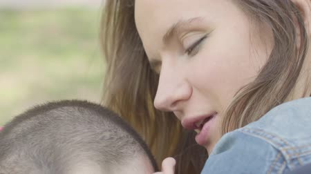 patting : Close up portrait cute mother hug young son and kiss him. Mothers love and care