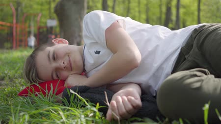 školák : Boy lying on the grass in the park near the playground upset or tired after school on a warm spring weekend day Dostupné videozáznamy
