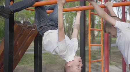 dvojčata : Two playful twins brothers training and playing on the horizontal bars on the playground in spring park
