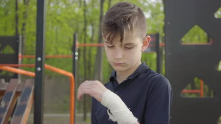 recess : Young boy with bandaged hand in the playground. Kid want to play but he is injured