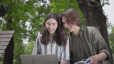 книгу : Portrait happy couple spending time together in the park, studying. The male and female students in casual clothes sitting at the bench, girl holding laptop and boy has journal in hands. Leisure outdoors.