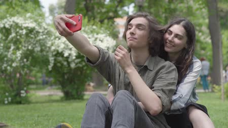 dinlenmek : A cute couple of students taking selfie sitting on the grass in the park. The guy is in the foreground, the girl hugging him from behind. Summertime leisure. Addiction to gadgets