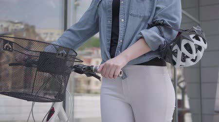 tegenhouden : Unrecognized young sport slim attractive blond woman in white jeans leading her bicycle near the shop windows in the city. The hot lady spending time outdoors, active lifestyle. Camera moving up