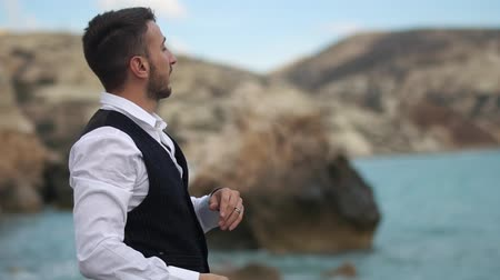 descobrir : Bearded handsome young man near the sea and mountains throwing stones in the water. Slow motion. Cyprus. Paphos Vídeos