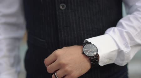 dependência : Man in classical suit looking at his watch on his hand. Man have a marriage ring on his hand. Watching the time.