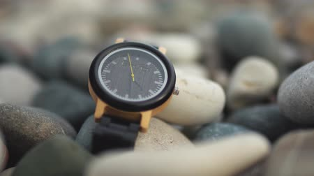 punctuality : Luxury black Watch with black watch strap on the beach stones.